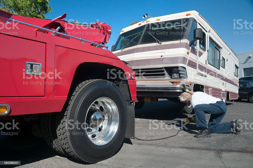 Tow Truck Driver Working on Broken Down Motor Home royalty-free stock photo
