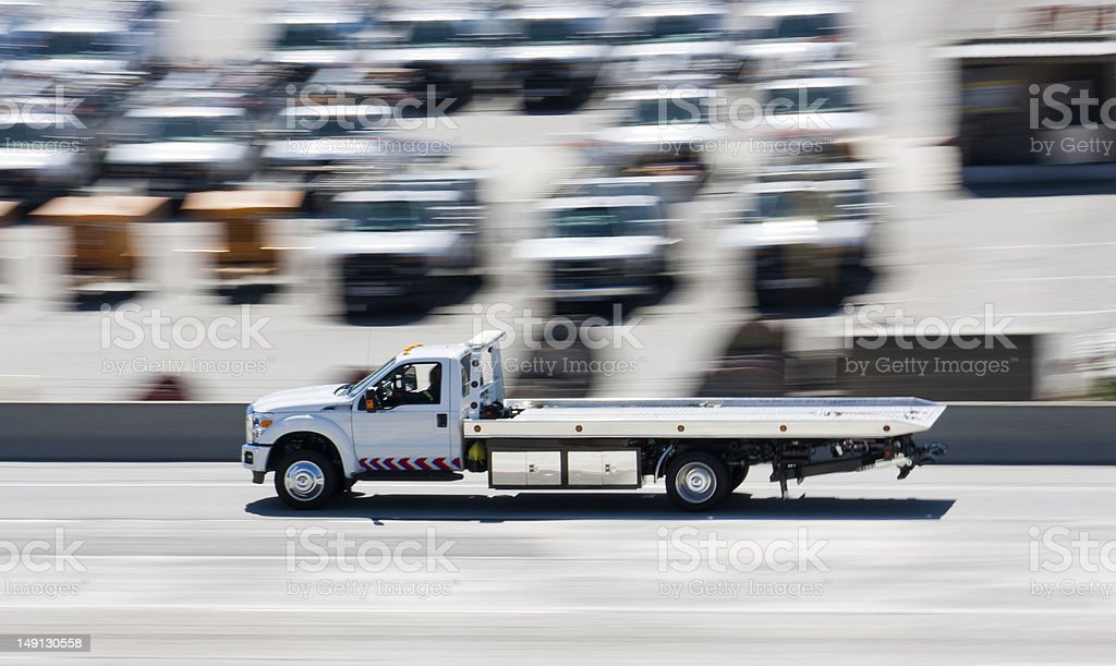 Tow truck driving down the highway with motion blur stock photo
