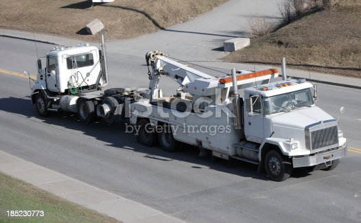 Big semi truck tow by heavy tow truck.