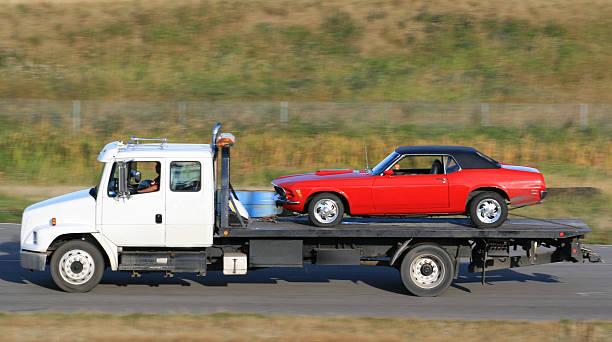 abschleppwagen heben ein neuen roten auto - was bringt unglück stock-fotos und bilder