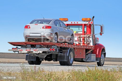 Rear quarter view of a red tilt bed tow truck on a highway carrying a nondescript vehicle.