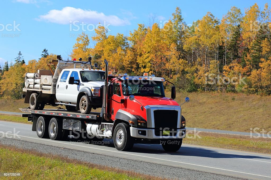 Tow truck with a truck aboard. stock photo