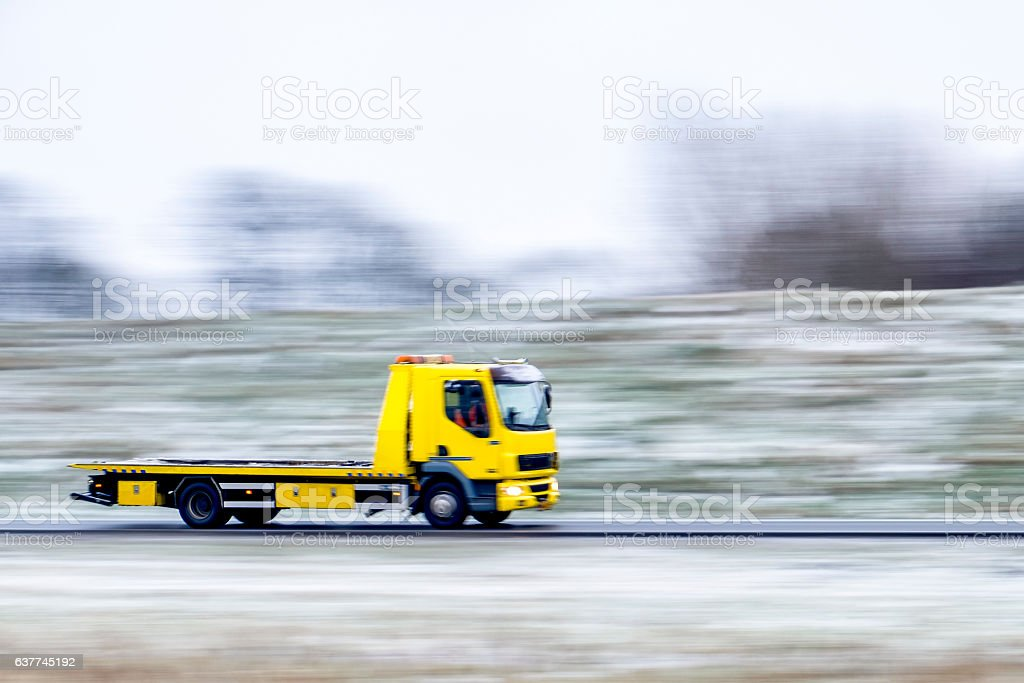 Tow Truck with an empty flatbed driving fast stock photo