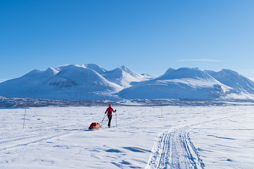 Cross country skier with sled (pulka) on a lake enjoying the view at the Ahkka mountain. Lapland,  Sweden.