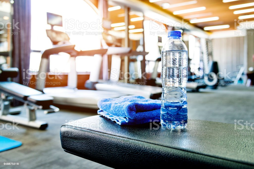 Towel and a bottle of water in gym stock photo