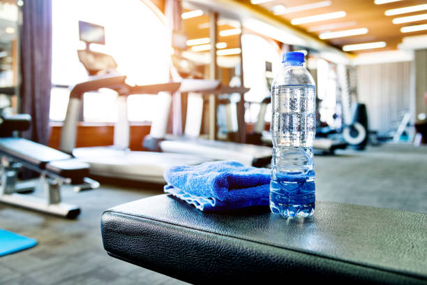 towel and a bottle of water in gym - health club stock photos and pictures