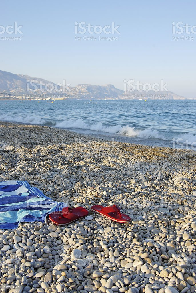 Towel and Flip-Flops on Beach. Vertical stock photo royalty-free stock photo