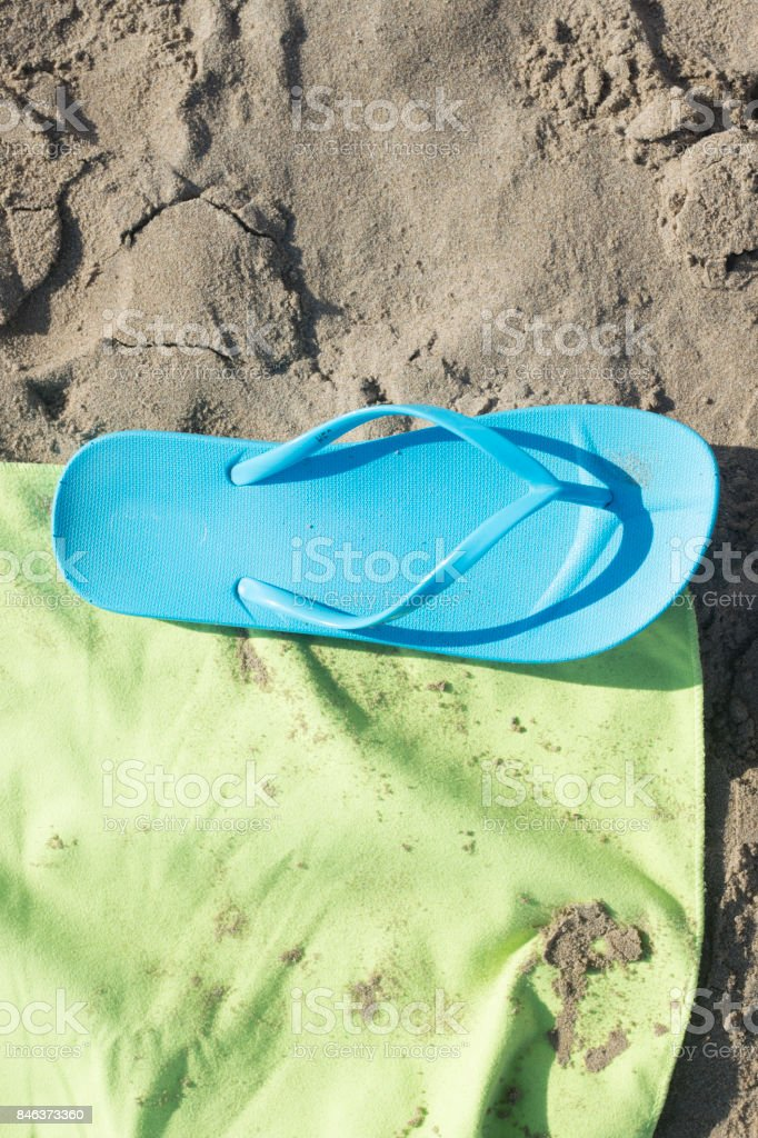 Towel and sandals on sandy  beach by the ocean on hot summer day. stock photo