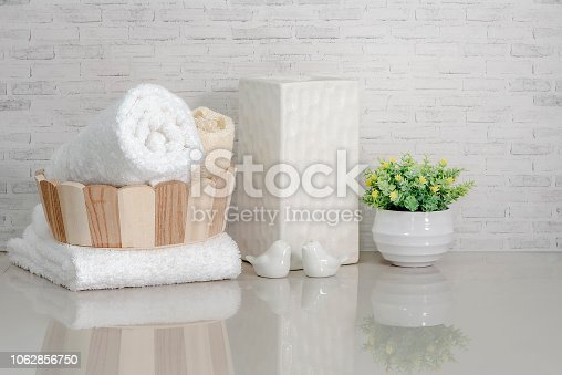 istock Towel in wooden bucket with ceramic vase, ceramic bird and houseplant on white marble teble 1062856750