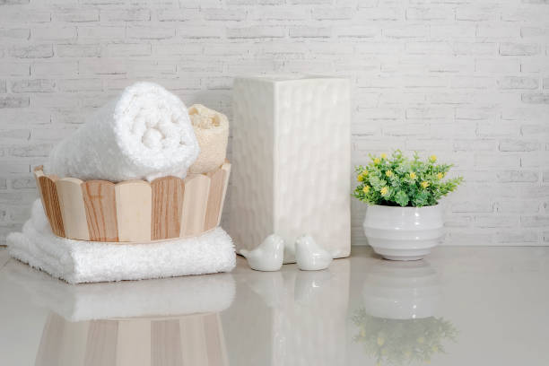 Towel in wooden bucket with ceramic vase, ceramic bird and houseplant on white marble teble Towel in wooden bucket with ceramic vase, ceramic bird and houseplant on white marble teble with brick wall background. white marble stock pictures, royalty-free photos & images