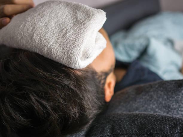 Towel on forehead, on man feels sick stock photo