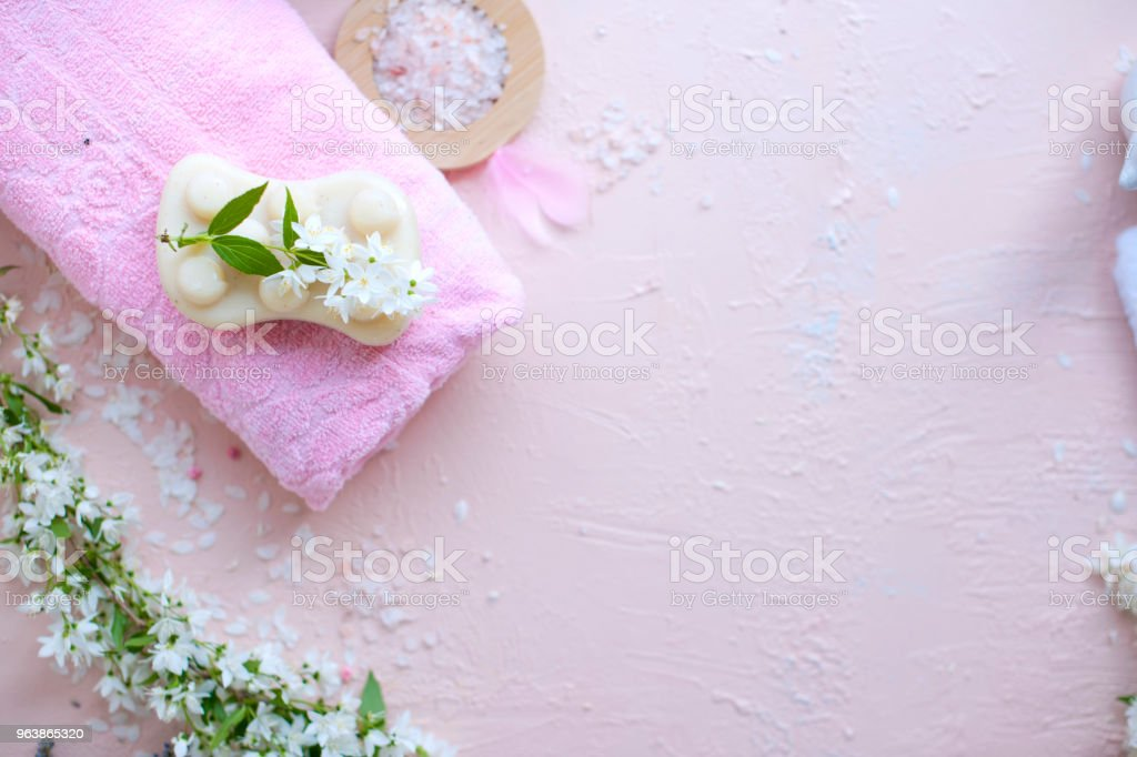 SPA. Towel, sea salt and soap. The flowers are white. Pink background. Place for text . - Royalty-free Archival Stock Photo