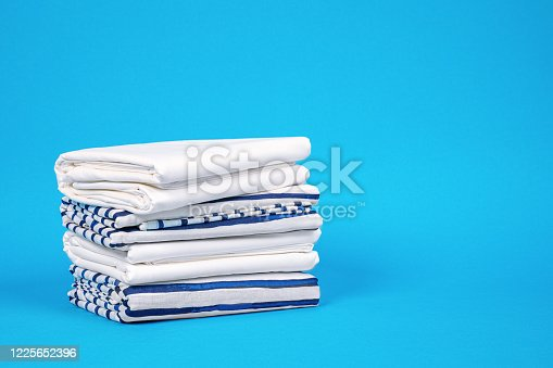 1146468307 istock photo Towels and bed linen with storage solution for wardrobe at home. Pillowcases and sheets neatly stacked on blue background, front view, copy space for lettering 1225652396