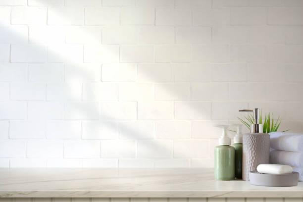 toalhas e champô ou sabão da cerâmica na tabela de mármore superior no fundo do banheiro. - banheiro instalação doméstica - fotografias e filmes do acervo