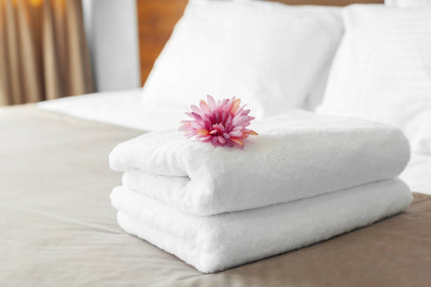 towels and flower on bed in hotel room - hotel foto e immagini stock