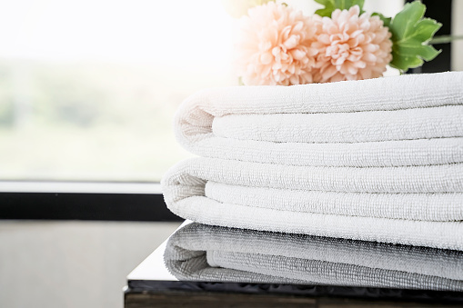 819534860 istock photo Towels and flowers on table with copy space. 1037974568