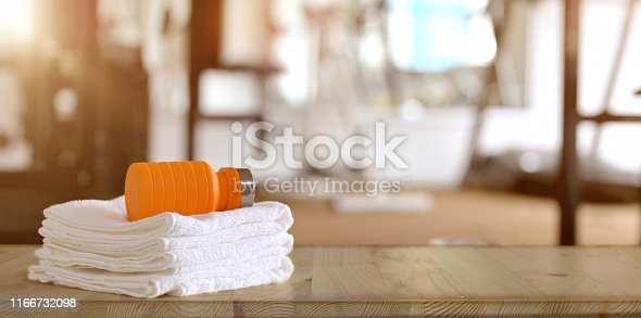 istock Towels and orange sport bottle with gym background 1166732098