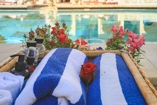 1131900491 istock photo towels and skin care bottles are on the basket near a swimming pool 1250076307