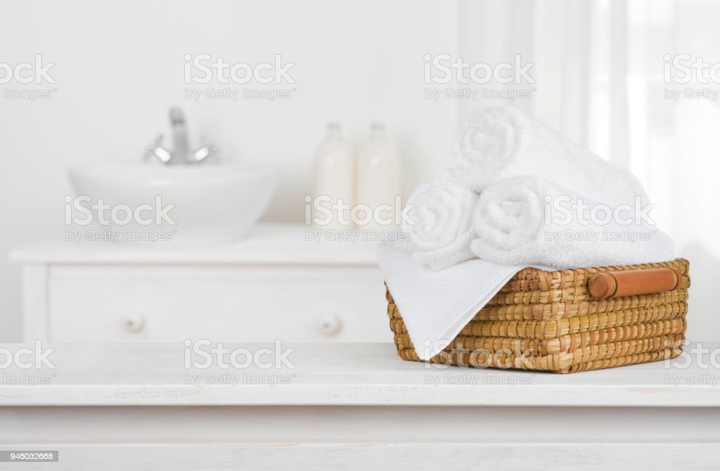 Towels basket on wooden table top with blurred bathroom interior stock photo