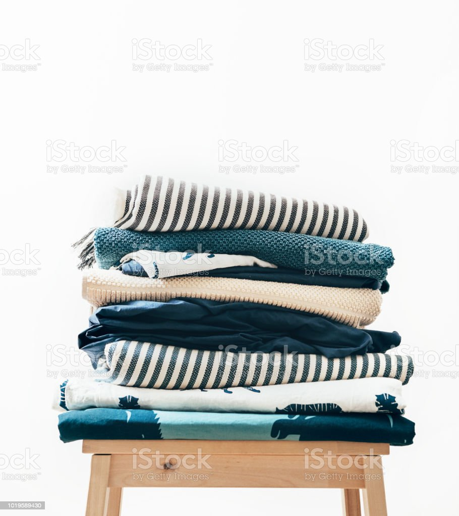 Towels, blankets and other home textile in blue and beidge colors are...