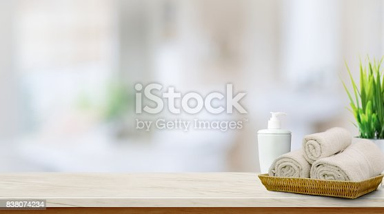 istock Towels in basket on top wood table with copy space on blurred bathroom background.