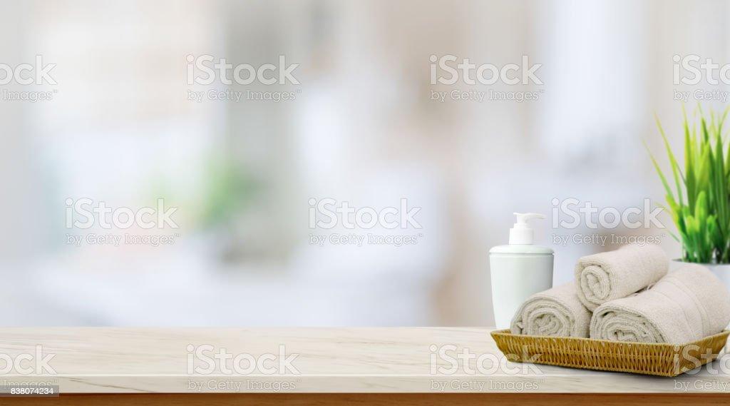 在籃子裡的但最高的木桌上與副本空間模糊的浴室背景上的毛巾。