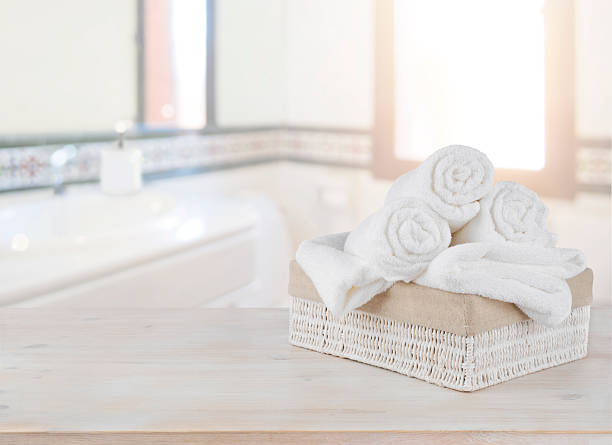 towels in basket on wooden table over defocused bathroom background - sonnendusche stock-fotos und bilder