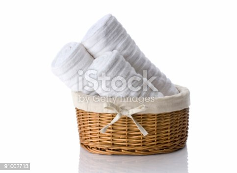 Three white hand towels in a wicker basket.