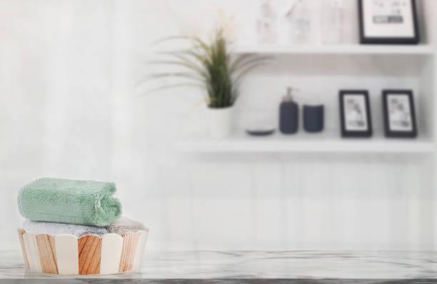 Toallas en cubo de madera en mesa de mármol en baño blanco con espacio de copia. - foto de stock