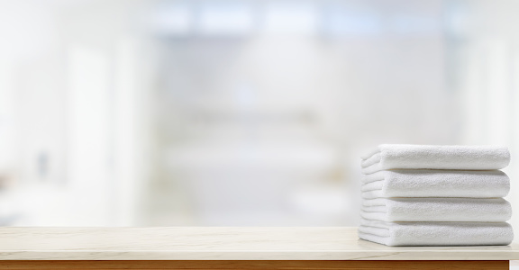 819534860 istock photo Towels on marble top table with copy space on blurred bathroom background. 829295678
