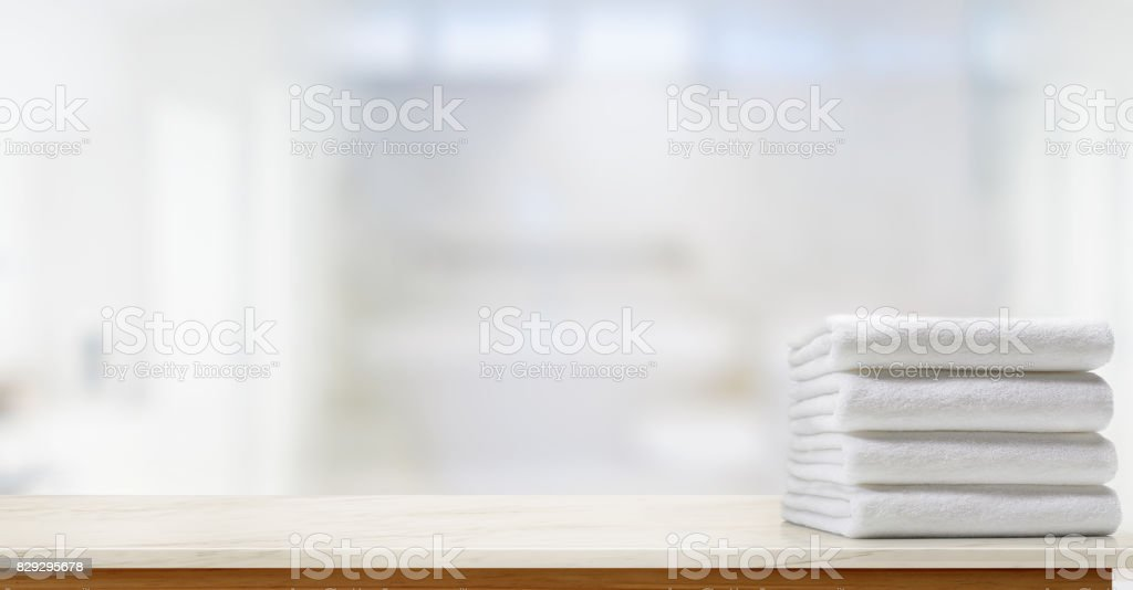 Towels on marble top table with copy space on blurred bathroom background. stock photo