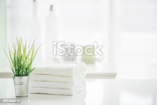 istock Towels on white table with copy space on blurred bathroom background 985388518