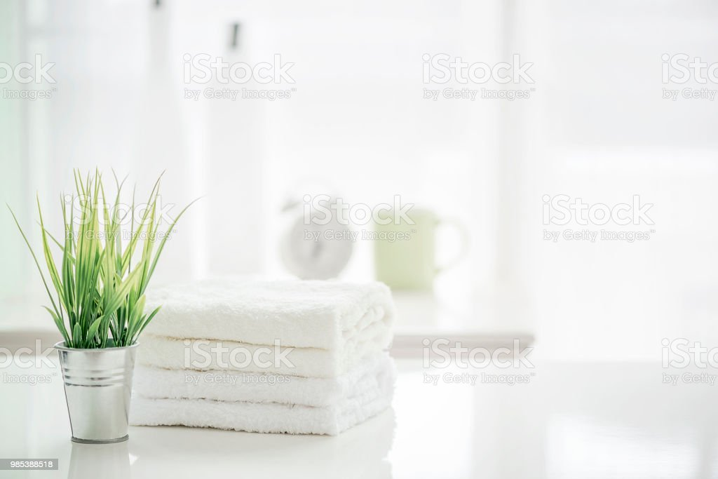 Towels on white table with copy space on blurred bathroom background stock photo