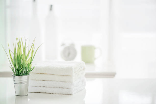 towels on white table with copy space on blurred bathroom background - спа стоковые фото и изображения