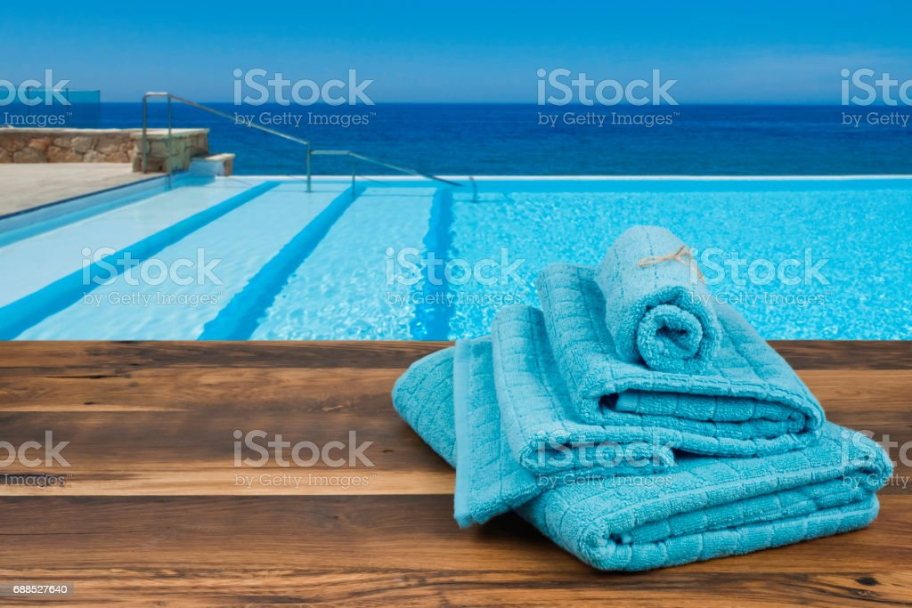 Towels on wooden over blurred swimming pool and sea background stock photo