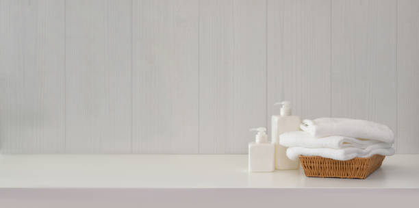 Towels with spa accessories on white table with copy space