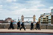 Some unrecognizable people cross London Bridge. London Bridge appears in the background.