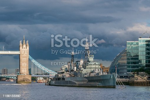 Tower Bridge, Thames and HMS Belfast (navy vessel). Sunny, but rain clouds in the distance