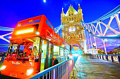 London, UK- February 4, 2017: View of Tower Bridge with tour bus passing by at night in London on February 4, 2017.