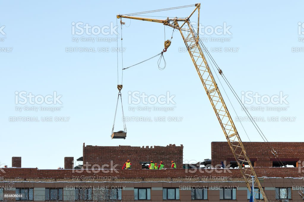 Tower crane and unidentified builders on the construction of building roof stock photo