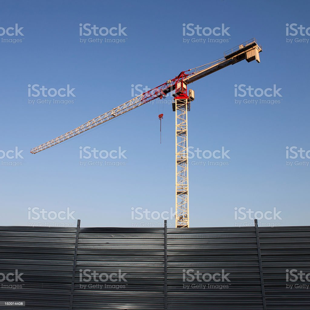 Tower crane and wall fence with blue sky stock photo
