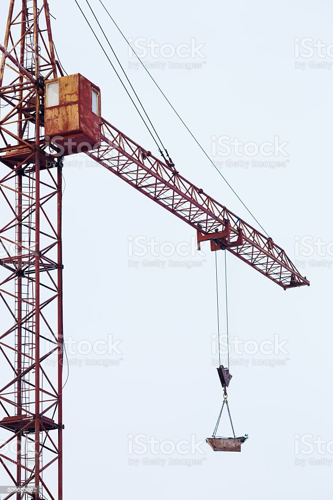 Tower crane carries load in bucket gas cylinders for cutting stock photo