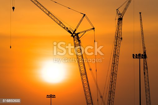 Tower crane on a construction site at sunset, Industrial construction cranes in silhouettes
