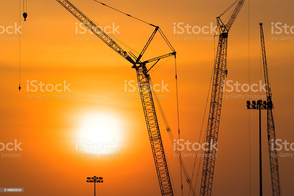 Tower crane on a construction site at sunset stock photo