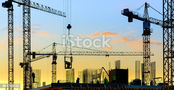 Industrial construction cranes and building silhouette with workers at sunset.