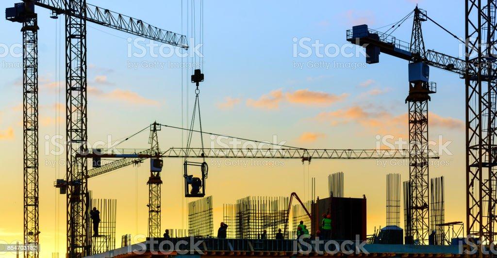Turmdrehkrane und Gebäude Silhouette mit Arbeitern bei Sonnenuntergang. – Foto