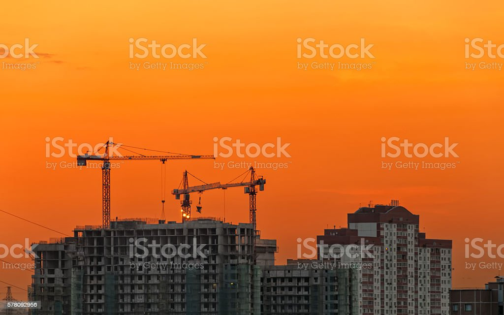 Tower cranes on construction site against evening glow background....