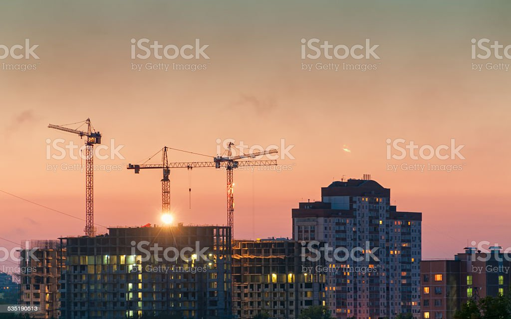 Tower cranes on construction site of modern buildings and skyscrapers...