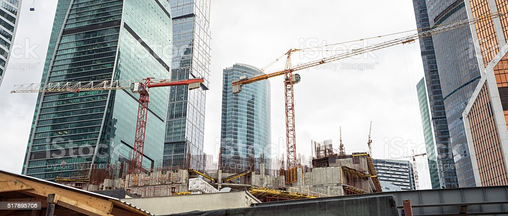 Tower cranes on construction site before skyscrapers stock photo