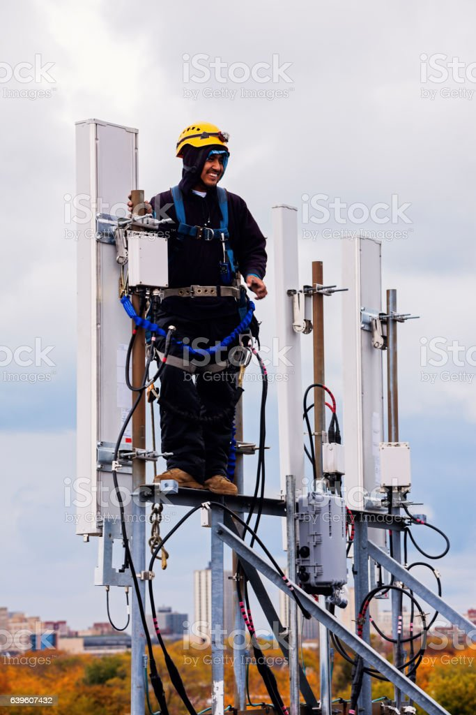 Tower crew leader working with the cellular antennas - Photo
